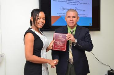 Minister of Public Health Dr. George Norton presents a plaque to President of Guyana Help The Kids (GHTK) Guyana Chapter, Dr. Winsome Scott
