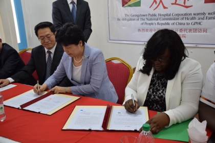 Minister within the Ministry of Public Health Dr. Karen Cummings and Vice Minister of National Health and Family Planning Commission of the People's Republic of China sign a certificate which takes into consideration the gifts that have been contributed to Guyana