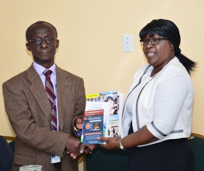 The Pan American Health Organisation/ World Health Organisation (PAHO/WHO) resident representative, Dr. William Adu-Krow hands over instructional and educational learning materials to Minister within the Ministry of Public Health, Dr. Karen Cummings