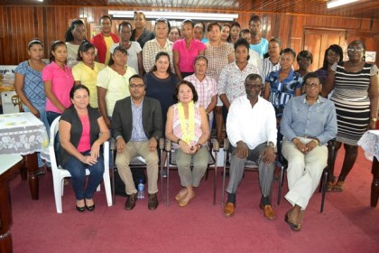 First Lady, Mrs. Sandra Ganger is flanked by, from left to right, facilitators of the Self Relaince and Success in Business Workshop, Ms. Marcia Meredith and Mr. Yohann Sanjay Pooran,  Regional Executive Officer, Mr. Brentnol Hopkinson and Lieutenant Colonel (ret'd) Ms. Yvonne Smith in the front row. The latest batch of participants in the workshop are pictured standing.