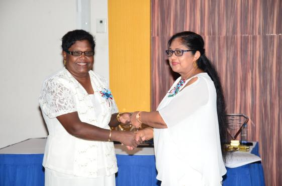 Mrs Sita Nagamootoo presenting a token of appreciation to Parbattie Rangall, Headmistress of Goed Fortuin Nursery. Rangall was one of several teachers who have attained 35 years of service and are still in the system.