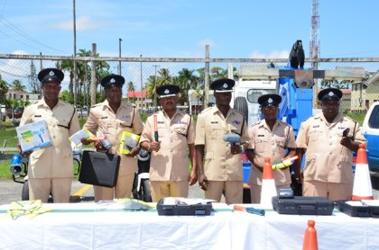 Traffic Chief, Dion Moore (centre) and ranks of the Guyana Police Force's Traffic Department with the newly acquired radar guns, breathalyser kits, flashing wands, traffic cones and reflector vests to be used in Operation Safeway.