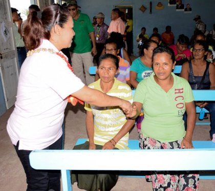 Minister in the Ministry of Communities, Dawn Hastings- Williams greets a resident at the meeting at White Water Multi-purpose Hall, Region One