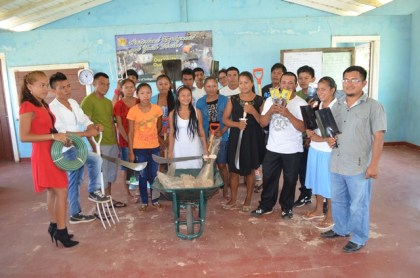 Some of the participants and facilitators of the Hinterland Employment and Youth Service (HEYS) programme with some agricultural tools received from Minister within the Ministry of Indigenous Peoples' Affairs, Valerie Garrido -Lowe