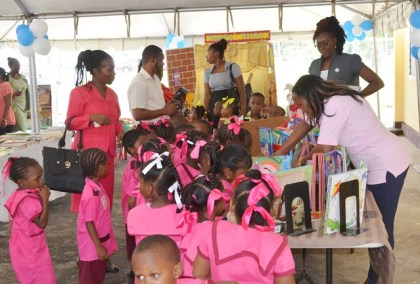 Children and teachers browse the teaching/learning materials on display at the Liana Nursery School