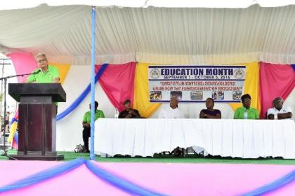 Minister of Education, Dr. Rupert Roopnaraine addressing the students. Seated at the head table from right: Chief Education Officer (ag) Mr. Marcel Hutson, Permanent Secretary, Ministry of Education, Ms. Delma Nedd, Minister within the Ministry of Education, Ms. Nicolette Henry and President David Granger.