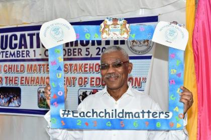 "President David Granger holding up the ""Each child matters"" slogan"