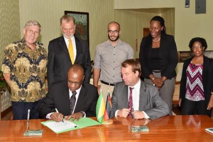 Minister of State, Mr. Joseph Harmon and Germany's Regional Director for Latin America and the Caribbean, Ambassador Dieter Lamle signing the agreement at the Ministry of the Presidency. Looking on are, from left: Mr. Ben Ter Welle, Ambassador Lutz Hermann Gorgens, Commissioner of the Protected Areas Commission (PAC), Mr. Damian Fernandes, Ms. Ndibi Schwiers-Ceres and Deputy Commissioner at the PAC, Ms. Denise Fraser