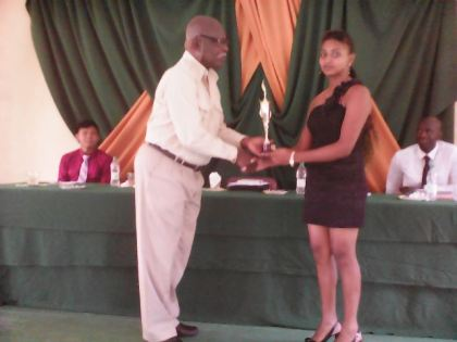 Minister of Citizenship, Mr. Winston Felix, hands over an award for Most Outstanding Personality to Ms. Priya Kissoon.