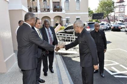 President Granger is welcomed to the Parliament Buildings by Speaker of the National Assembly, Dr. Barton Scotland OR and Prime Minister Moses Nagamootoo, upon his arrival.