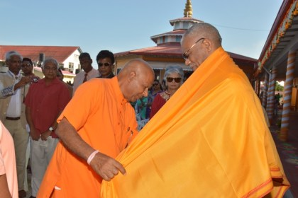Principal of the Saraswati Vidya Niketan (SVN) Hindu School, Swami Aksharananda wraps a shawl around President David Granger as part of the ceremonial welcome to the graduation ceremony.