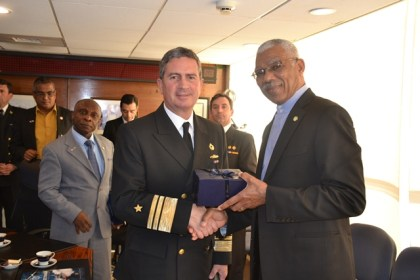 Director of Maritime and the Environment, Rear Admiral Osvaldo Schwarzenberg hands over a gift to President David Granger at the conclusion of the meeting.