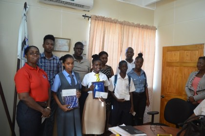 Some of the students who received Bursary Awards for Grade 6 Assessment and CSEC Exams with Chief Port Security Officer Dwain Nurse (White Shirt) and Director of Ports, Louise Williams (Red Shirt).