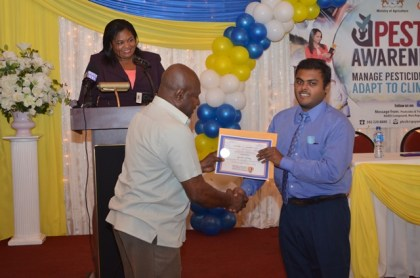 Chairman of the PTCCB, Dr. Leslie Munroe presents a certificate to a graduate, at the PTCCB Graduation Ceremony as Registrar of the PTCCB, Trecia Garnath (in Background) looks on