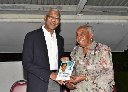 President David Granger receiving his copy of 'From Seedtime to Harvest' from Ms. Carmen Jarvis