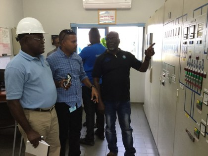 GWI's Georgetown Manager, Cutris Niles; Executive Director of Project Implementation & Partnership Building, Ramchand Jailal and ; Technical Advisor, Joseph Codette analyse a section of the operational setup at the Suriname Water Company.