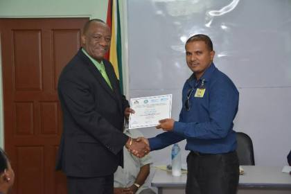 Minister of State, Mr. Joseph Harmon presents the Certificate of Pass to this participant from the Cheddi Jagan International Airport (CJIA)