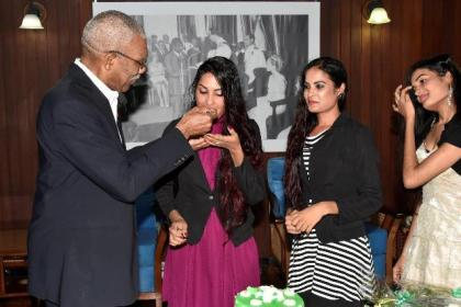 President David Granger gives Ms. Radha Mansaram a piece of her birthday cake as her sisters look on.