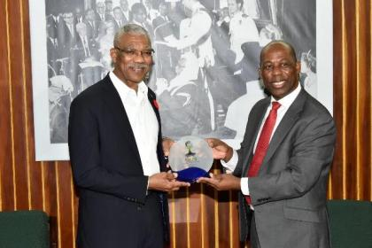 Reverend Dr. Collin Cowan presents a token to President David Granger at the conclusion of their meeting at the Ministry of the Presidency, earlier this evening.