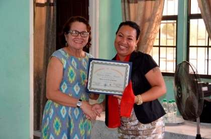 First Lady, Mrs. Sandra Granger presents a certificate to Ms. Gwencia Samaroo, who owns and operates a grocery store in Kuru Kururu.