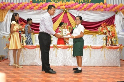 Best Graduating Student, Ms. Bibi Aseeya Mohamed receives her awards from one of the teachers at the graduation ceremony