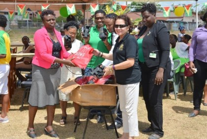 First Lady, Mrs. Sandra Granger presents a box of 'the shoes that grow' to a representative of the Kwakwani Primary School.