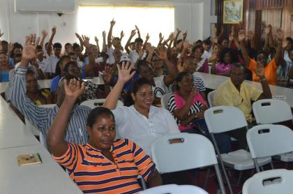 Residents of Lima Sands, Essequibo, Region Two all raise their hands in agreement to the change in age for the acquisition of houselots from 21 years to 18years