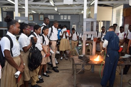 Youths look on as a welder showcases his skills