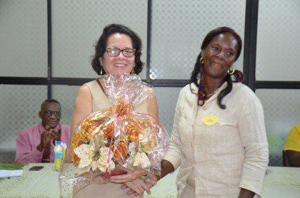 First Lady Mrs. Sandra Granger smiles after receiving a bouquet from graduate Ms. Cathy McNabb at the graduation ceremony.