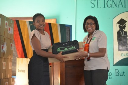 Head of the Information Technology Department of the St Ignatius Secondary, Abeena Benn collects her laptop device from Minister of Telecommunications, Catherine Hughes at the distribution exercise at the St Ignatius Secondary School