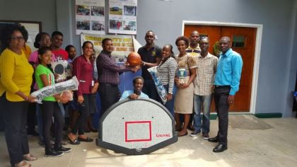Director of Sports, Christopher Jones hands over the sport gear to representatives of the University of Guyana's Tain campus