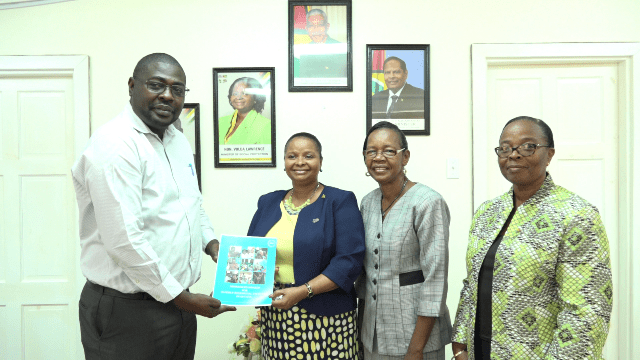 Director, Social Services, Whentworth Tanner presenting a copy of the Minimum standards for elderly homes in Guyana to Minister of Social Protection, Volda Lawrence. Secretary of the Commission for the Elderly, Yvette De Leon and Permanent Secretary, Ministry of Social Protection, Mrs. Lorene Baird (right) are also in photo