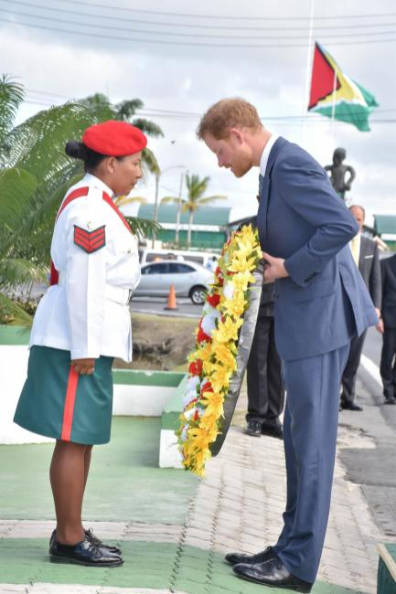 Prince Harry collects the remembrance wreath from a member of the Guyana Defence Force. He later laid it at the feet of the Independent Arch at Brickdam