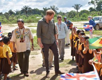 Students of Fairview village welcome Prince Harry. Also in photo are Minister of Indigenous Peoples' Affairs, Sydney Allicock and British High Commissioner to Guyana, Greg Quinn