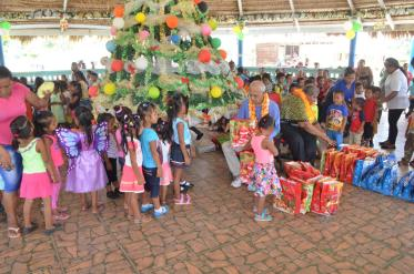 Minister of Communities Ronald Bulkan distributes gift to the students at the Christmas Party in Micobie