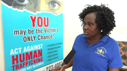 Acting Coordinator, C-TIP Unit, Tanisha Williams-Corbin displaying the banner that will be used to create awareness at key areas to fight  human trafficking