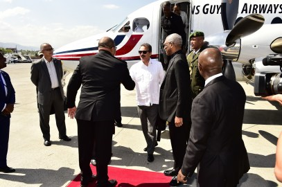 President David Granger, today, arrived in Haiti to attend the Inauguration Ceremony of the President elect of the Republic of Haiti, Mr. Jovenel Moise. On his way there, he briefly stopped over at Antigua and Barbuda, where he was greeted by Haiti's Foreign Minister, Mr. Pierrot Delienne (backing camera) and Minister of Foreign Affairs of Antigua and Barbuda, Mr. Charles Fernandez (white shirt)