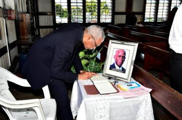 President David Granger signing the Book of Condolence for the late Mr. Noel Gordon Sinclair