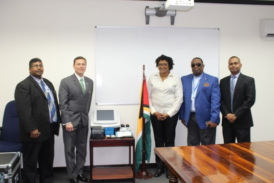 Minister within the Ministry of Public Infrastructure, Hon. Annette Ferguson (third right) and Mr. Terry Steers-Gonzalez, Deputy Chief of Mission of the United States Embassy, with the equipment following the simple handing over ceremony. With them are Lt. Col. (Ret'd) Lawrence London, Chairman of the GCAA's Board (second right); Mr. Abraham Dorris, Manager of the Aviation Security Dept. of the GCAA (First left); and Mr. Alvin Majeed, Airport Security Manager of the Cheddi Jagan International Airport Corporation (CJIAC) (right)