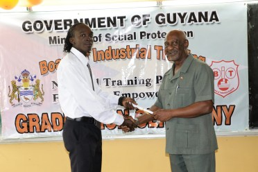 Minister within Social Protection Keith Scott presenting certificate to Orlando Davidson, best graduating student