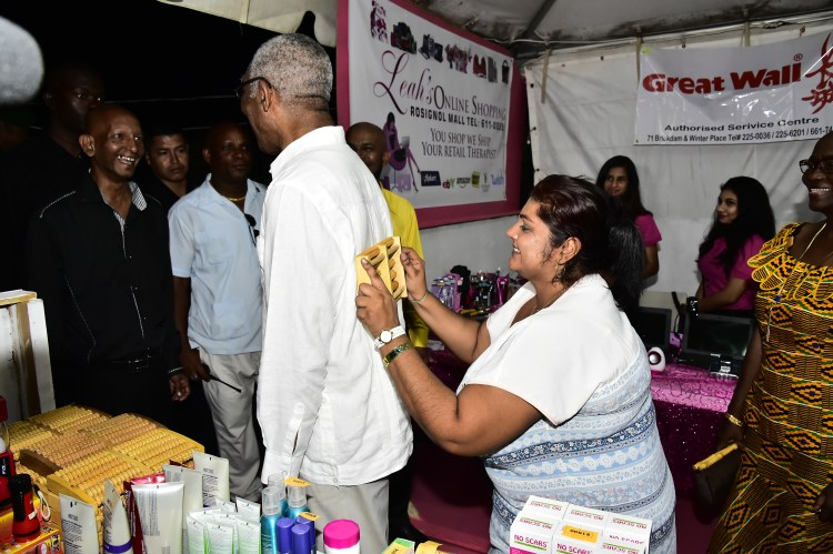 Owner of the Body Relaxation Massage Spa and Salon, Ms. Samantha Davi Thuknauth demonstrates how this wooden massage tool works for President David Granger
