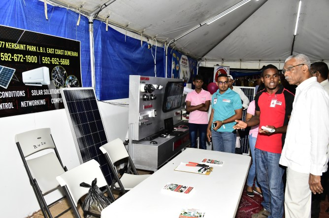 President David Granger listens as Head Field Technician, Mr. Akiem Yanvield describes the solar panel sale and installation services offered by Smart Tech Solutions