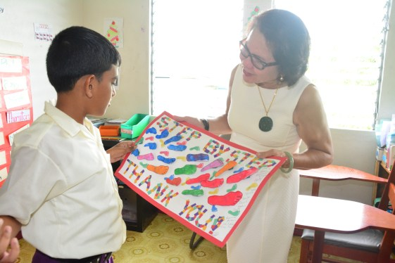 Student Shoaib Khan interacts with First Lady, Mrs. Sandra Granger after presenting her with a large thank you card