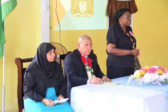 Ms. Natasha Singh-Lewis, Technical Officer and Minister of Social Cohesion, Dr. George Norton, both pay keen attention while Ms. Genevieve Allen, Chairman of the Regional Democratic Council, Demerara-Mahaica, delivers her address