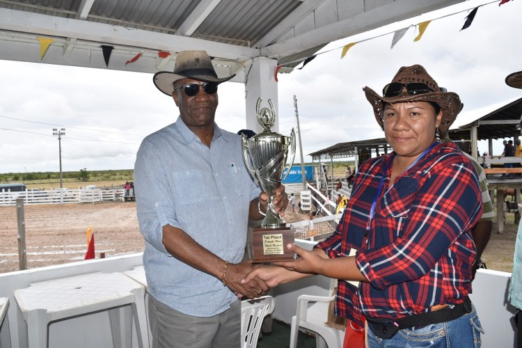 Minister of State, Mr. Joseph Harmon making a contribution to the Rupununi Rodeo. Receiving the trophy on behalf of the Rodeo Committee is Ms. Rebecca Faria