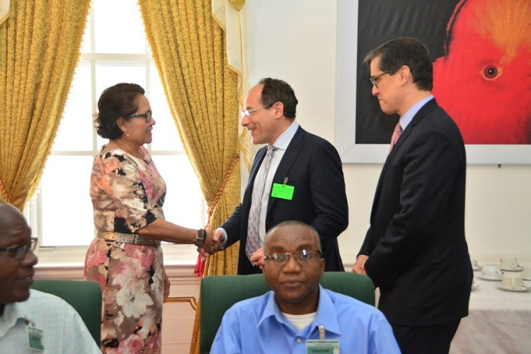 First Lady, Mrs. Sandra Granger shakes hands with Mr. Barry Featherman, Senior Director, Government Affairs as Mr. Rafael Campos, Senior Product Manager, both of GILEAD Sciences Incorporated look on. Mr. Oneil Atkins, Advisor to the Minister of Public Health on Pharmaceuticals is pictured prominently in the foreground. Member of Parliament, Mr. John Adams, who is also an Advisor to the Minister of Public Health, is pictured partially, first, left