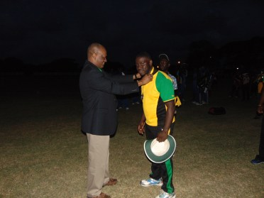 Minister Harmon giving medal to the winning team