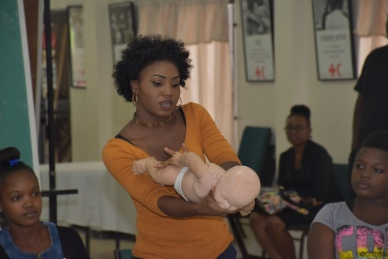 Ms. Shanice Edwards demonstrates how to treat a choking baby or toddler, during the interactive session of the closing ceremony of the First Aid, Cardiopulmonary Resuscitation (CPR) and the use of the Automated External Defibrillator (AED) training workshop