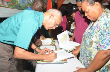Minister of Communities, Ronald Bulkan, signing the Local Government Handbooks presented to Councilors from various Municipalities
