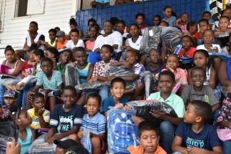 Minister Broomes pose with the children and their school gears